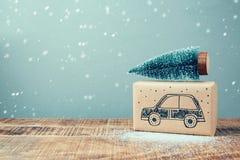 圣诞节有汽车图画的节日礼物箱子和在木桌上的杉树 免版税库存照片