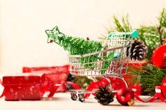 圣诞节有玩具树和红色当前箱子的购物台车 免版税库存图片