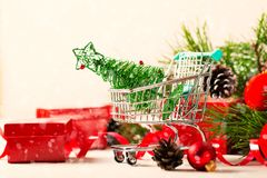 圣诞节有玩具树和红色当前箱子的购物台车 库存图片