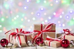 圣诞节有球的礼物盒反对bokeh背景 3d美国看板卡上色展开标志问候节假日信函国民形状范围 图库摄影