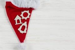 圣诞节有简单的木玩具的圣诞老人帽子在白色土气木头 免版税库存照片