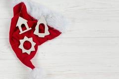 圣诞节有简单的木玩具的圣诞老人帽子在白色土气木头 库存图片