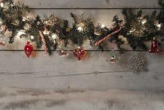 圣诞节有红色中看不中用的物品、棒棒糖和装饰品的杉树诗歌选,垂悬在老木板背景 免版税库存照片