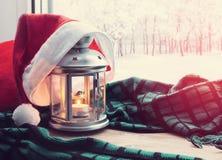 圣诞节有蜡烛的冬天背景灯笼和在窗台的圣诞老人帽子与外面冬天自然 免版税库存图片