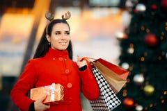 圣诞节有袋子和礼物盒的女售货员 图库摄影