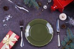 圣诞节服务桌-板材,玻璃,灯,蜡烛,杉木锥体,礼物盒 顶视图 与大方的本体空间的土气背景 免版税库存图片