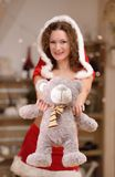 圣诞节服装的圣诞老人女孩有逗人喜爱的玩具熊的 免版税库存图片