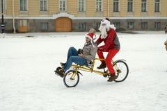 圣诞节服装的骑自行车者 免版税库存照片