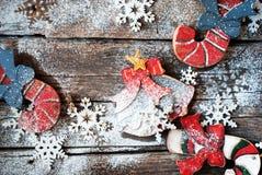 圣诞节木杉树戏弄棒棒糖、响铃和雪花在书桌上 免版税库存图片