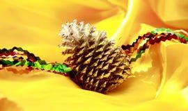 圣诞节杉木锥体在黄色装饰 免版税库存照片
