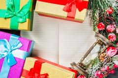 圣诞节杉树分支,礼物盒,结冰的红色莓果、锥体和葡萄酒滴漏框架在笔记本有拷贝空间的文本的 免版税图库摄影