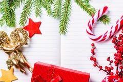 圣诞节杉树分支,装饰、天使、棒棒糖,结冰的红色莓果、星和礼物盒框架在笔记本,拷贝空间 免版税图库摄影