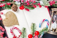 圣诞节杉树分支,装饰、天使、棒棒糖,结冰的红色莓果、锥体和葡萄酒滴漏框架在笔记本, co 免版税图库摄影