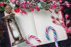 圣诞节杉树分支,装饰、棒棒糖,结冰的红色莓果、锥体和葡萄酒滴漏框架在笔记本有雪的, 免版税库存照片