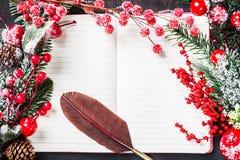 圣诞节杉树分支,装饰,棒棒糖,结冰的红色莓果,与老葡萄酒翎毛钢笔框架的锥体在笔记本,拷贝 库存照片