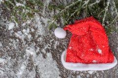 圣诞节杉树和红色帽子在一个木板有雪的,绿色框架chistmas的 库存图片