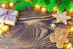 圣诞节杉树用自创姜饼曲奇饼、礼物和光在老木背景与空间文本的 快活的Christma 免版税图库摄影