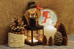 圣诞节来 被点燃的蜡烛、黑金属灯笼、冷杉球果、木烟囱扫除机和雪人在红色帽子有响铃agai的 免版税库存照片