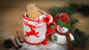 圣诞节杯和一个玩具雪人在木背景 免版税图库摄影