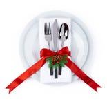 圣诞节板材和银器与在白色隔绝的红色丝带 免版税库存图片