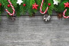 圣诞节构成用冷杉分支、装饰、糖果和杉木锥体做了在木桌 背景上色节假日红色黄色 库存照片