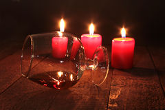 圣诞节构成用玻璃科涅克白兰地、礼物盒和蜡烛在木桌上 免版税库存图片