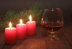 圣诞节构成用玻璃科涅克白兰地、礼物盒和蜡烛在木桌上 免版税库存照片