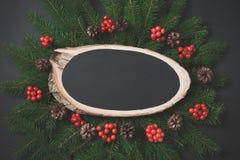 圣诞节构成由圣诞树制成分支,与木锯的红色莓果作为在黑色的空的空白 表面无光泽的图象 库存照片