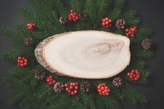 圣诞节构成由圣诞树制成分支,与木锯的红色莓果作为在黑色的空的空白 表面无光泽的图象 图库摄影