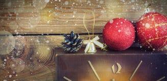 圣诞节构成红色和黄色球,锥体,在一个篮子的老时钟在木背景 例证百合红色样式葡萄酒 定调子 免版税库存照片