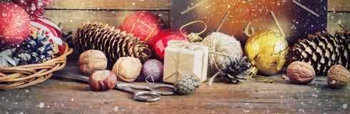 圣诞节构成红色和黄色球,锥体,在一个篮子的老时钟在木背景 例证百合红色样式葡萄酒 定调子 免版税图库摄影