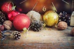 圣诞节构成红色和黄色球,锥体,在一个篮子的老时钟在木背景 例证百合红色样式葡萄酒 定调子 库存照片