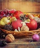 圣诞节构成红色和黄色球,锥体,在木背景的一个篮子 例证百合红色样式葡萄酒 定调子 免版税库存照片