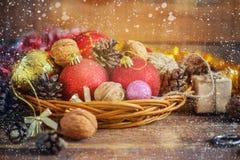圣诞节构成红色和黄色球,锥体,在木背景的一个篮子 例证百合红色样式葡萄酒 定调子 免版税库存图片