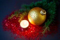 圣诞节构成-金黄球、云杉的分支和一个灼烧的蜡烛 免版税图库摄影