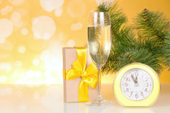 圣诞节树分支、一杯香槟,礼物盒和大约十二个小时 库存照片