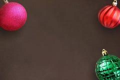 圣诞节桃红色,红色波浪和绿色有肋骨球在黑暗的木桌上 图库摄影