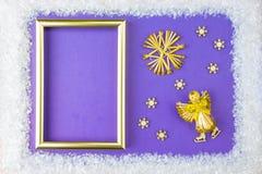圣诞节框架包括白色点缀:雪花、驯鹿、天使飞行和礼物盒在蓝色 免版税图库摄影