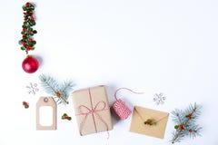 圣诞节框架构成 圣诞节礼物、杉木分支、红色球、信封、白色木雪花、丝带和红色莓果 名列前茅v 库存照片