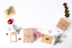 圣诞节框架构成 圣诞节礼物、杉木分支、红色球、信封、白色木雪花、丝带和红色莓果 名列前茅v 库存图片