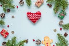 圣诞节框架由冷杉分支、红色莓果、礼物盒和杉木锥体做成与被编织的心脏 库存照片