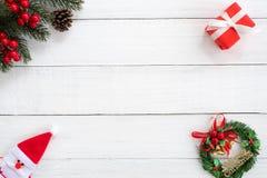 圣诞节框架由冷杉分支、霍莉莓果和红色礼物盒制成有装饰的在白木委员会 图库摄影