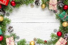 圣诞节框架由冷杉分支做成、红色和金黄装饰、礼物盒和杉木锥体 库存图片