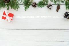 圣诞节框架由冷杉叶子、杉木锥体和红色礼物盒制成有装饰土气元素的在白色木 免版税图库摄影