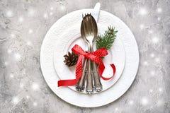 圣诞节桌与圣诞节杉木的餐位餐具分支和p 免版税库存照片