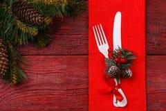 圣诞节桌与红色餐巾的餐位餐具、白色叉子和刀子、槲寄生装饰的小树枝和圣诞节杉木 免版税库存照片