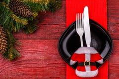 圣诞节桌与红色餐巾的餐位餐具、黑色的盘子、白色叉子和刀子、装饰的圣诞老人夹克和圣诞节 免版税库存照片