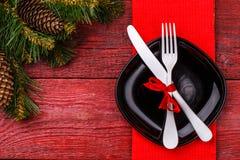 圣诞节桌与红色餐巾的餐位餐具、黑色的盘子、白色叉子和刀子、装饰的红色弓和圣诞节杉木 图库摄影