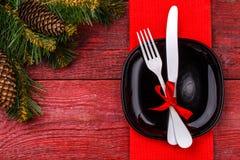 圣诞节桌与红色餐巾的餐位餐具、黑色的盘子、白色叉子和刀子、装饰的红色弓和圣诞节杉木 库存照片
