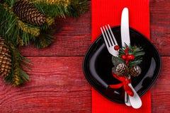 圣诞节桌与红色餐巾的餐位餐具,黑色的盘子、白色叉子和刀子,槲寄生装饰的小树枝和 库存图片